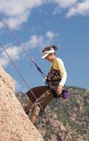 senhora sênior na subida íngreme da rocha em colorado