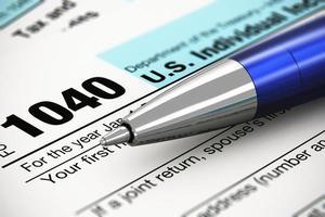 o 1040 nos formulário de imposto de retorno individual e caneta esferográfica foto