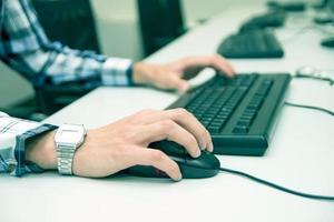 close-up das mãos do homem usando o teclado e o mouse do computador foto