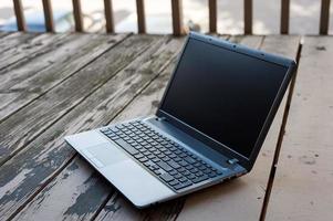 computador portátil aberto com tela preta no pátio de madeira fora foto