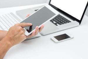 mãos de homem segurando o tablet com fundo de computador portátil