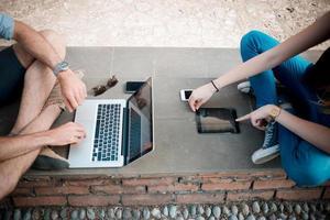 jovem casal usando a tecnologia multitarefa smarpthone tablet e foto
