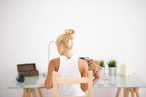 mulher loira usando seu laptop. vista por trás foto
