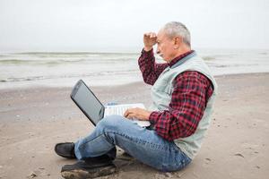 velho com notebook na praia foto