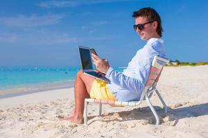 jovem empresário usando laptop e telefone na praia tropical foto