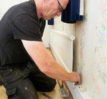 encanador drenando e removendo um radiador antigo em uma propriedade