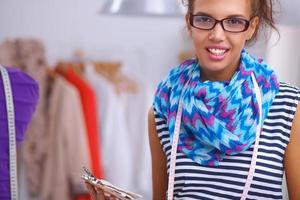 designer de moda sorridente em pé perto de manequim no escritório foto