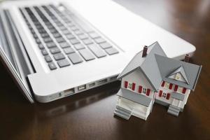 casa em miniatura e computador laptop foto