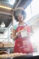 empregado no avental vermelho, segurando a caixa foto
