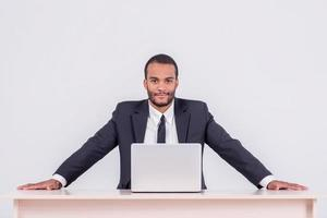 o trabalho está feito. sorridente empresário Africano sentado foto