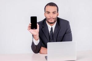 telefone celular e empresário. sorridente empresário africano sentado foto