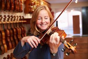 cliente experimentando violino na loja de música foto