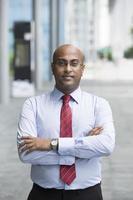 homem de negócios indiano confiante em pé na cidade moderna foto