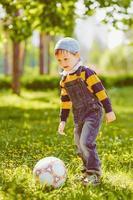 menino brincando com bola de futebol no parque foto