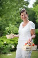 mulher no jardim segurando ervas e legumes foto