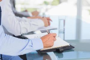 equipe de negócios, anotando-se durante a conferência foto