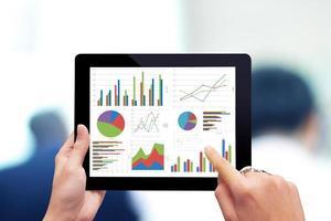 close-up de mãos masculinas tocando tablet com diagrama comercial foto