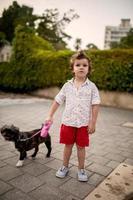 menino bonitinho com um cachorro na rua. foto