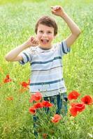 menino no prado de papoula flor vermelha se divertir foto