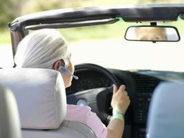 mulher com dispositivo mãos-livres no carro, vista traseira foto