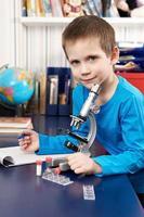 menino com microscópio em casa foto