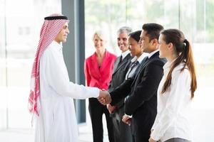 aperto de mão do empresário árabe com seus funcionários foto