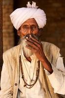 velho indiano, fumando um cigarro foto