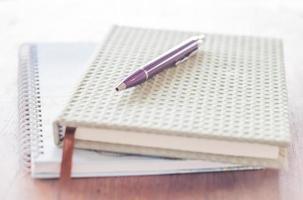 caneta e dois cadernos na mesa de madeira foto