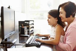 mulher hispânica sênior com computador e neto