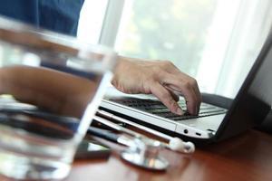 médico trabalhando com tablet digital e computador portátil foto