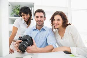 trabalho em equipe feliz posando com câmera digital foto