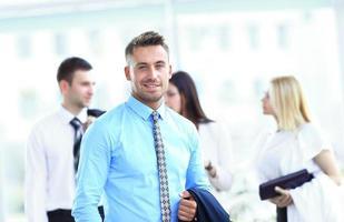 homem de negócios feliz bonito com colegas na parte de trás foto