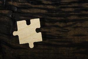 quebra-cabeça de madeira em fundo escuro.