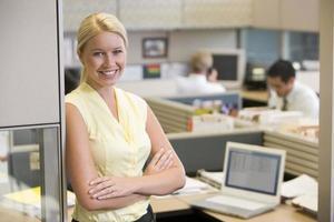 mulher sorridente com os braços cruzados em pé no escritório foto