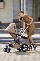 mãe moderna elegante numa rua urbana com um carrinho de bebê. foto
