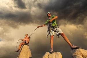 marido e mulher escalando equipe no cume.