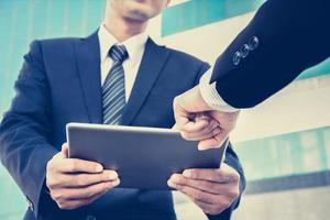 empresários, olhando para o tablet pc com uma mão tocando a tela foto