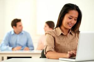 mulher asiática adulta trabalhando em seu laptop foto