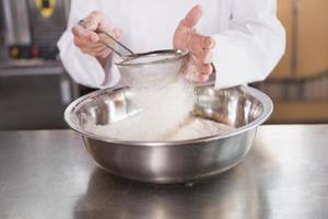 padeiro peneirar farinha em uma tigela foto