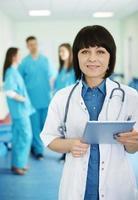 retrato da médica com estagiários em segundo plano foto