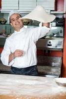 chef jogando a massa base de pizza foto