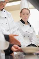 chef de mulher pensativa olhando um prato foto