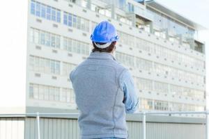 arquiteto usando capacete enquanto olha para a construção foto