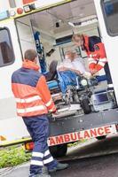 paramédicos colocando paciente em ambulância carro ajuda foto