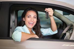 mulher sorridente, segurando a chave do carro foto