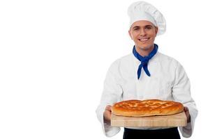 jovem padeiro detém um pão na tábua de pão foto