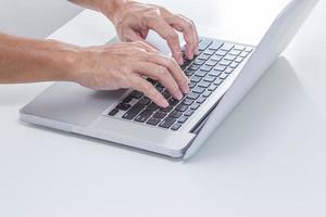 mãos de homem, digitando o teclado do laptop foto