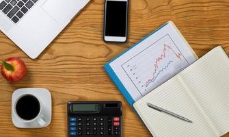 desktop com computador e equipamento financeiro para analisar finanças foto