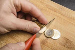 mão corta moedas de euro com faca na tábua foto