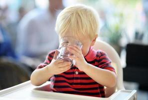 criança menino água potável foto